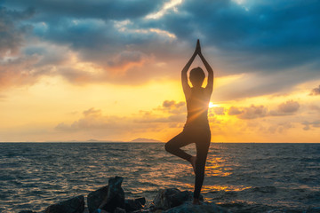 Meditation girl on the sea during sunset. Yoga silhouette. Fitness and healthy lifestyle