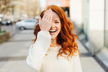 Laughing playful young woman covering one eye