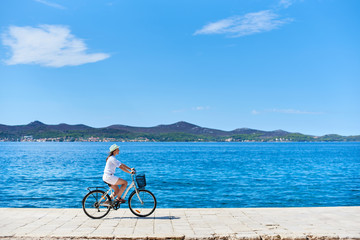 Young woman in white summer closing and hat riding a bicycle along stony sidewalk on blue sparkling sea water and resort town at foot of mountains on opposite shore background. Tourism and vacations.