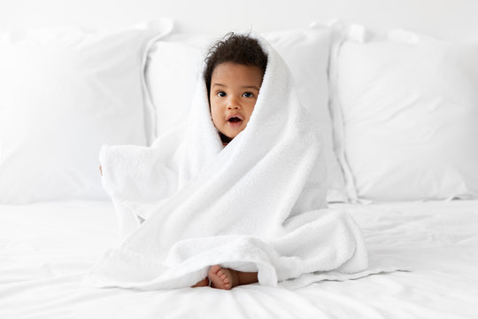 Black baby sitting on bed wrapped in towel after bath