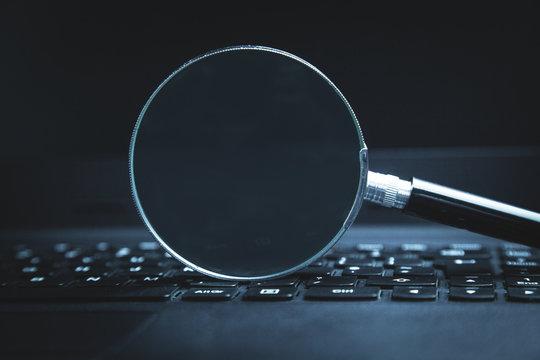 Magnifier on laptop keyboard. Searching on internet