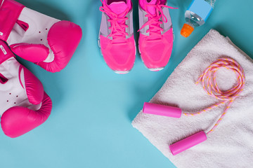 sport clothes and accessories background - pink boxing gloves, jump rope, blue background  - Image