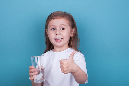 Cute little girl drinking water from glass on blue background