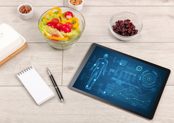 Healthy food composition with tablet. Body diagnosis on the screen