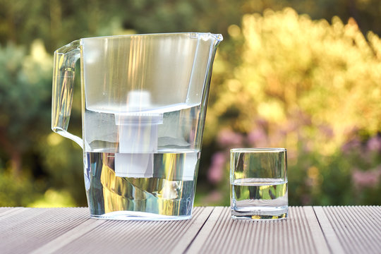 Water filter pitcher and a clean glass of a clear water close up on the summer garden background