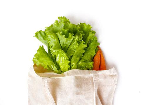 fresh vegetables lettuce leaves and carrots in a linen bag for shopping