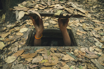 girl going into narrow and small Cu Chi tunnel built by vietnamese guerilla forces during Vietnam war, 60 km from Ho Chi Minh City,