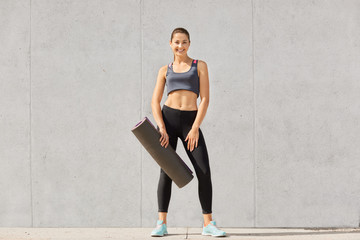 Attractive beautifull young sportswoman wearing top, leggins and sneakers, with pony tail, holding yoga mat, has workout, training indoor, isolated over grey background. Health care concept.