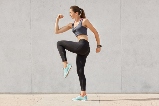Young sporty woman doing exercise against gray background, dressed top, leggins, sneakers, has pony tail, raises legs, has intense workout, keeps fit, preapres for running or jogging. People and sport