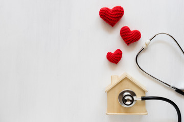 Home saving with Heart made of red yarn on white background. Home insurance concept.