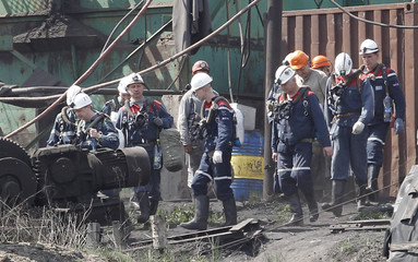 Miners and rescuers walk at a coal mine following a methane explosion near Luhansk