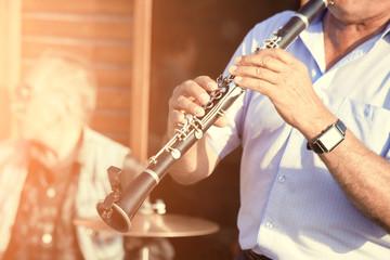 man playing clarinet on street