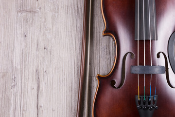 Detail of classical violin isolated on wooden background. Studio shot of old violin. Classical musical instrument