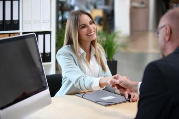Junge Frau wird zu einem Bewerbungsgespräch begrüsst
