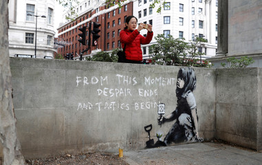 A passer-by takes a photograph next to a graffiti believed to have been created by street artist Banksy, at the site where hundreds of Extinction Rebellion climate protestors camped recently, at Marble Arch in London