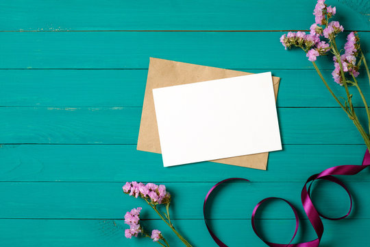 Blank greeting card and envelope with purple daisy flowers on green wooden table. Flat lay composition, top view, overhead.