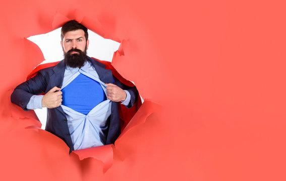Through paper. Business growth. Businessman. Bearded man looking through paper. Super businessmen showing blue shirt. Superhero. Superman Cape. Hero. Symbol S. Super power.
