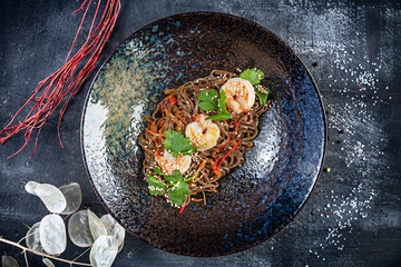 Top view on buckwheat Thai noodles with shrimps served in black textured plate on dark background. Flat lay thai cuisine. Seafood. Reaydy for eat. Picture for recipe. Copy space for design