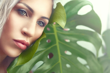 A girl with gray eyes and blond hair holds a tropical leaf monstera near her face. Dreamy look. Fantasies and memories of summer holidays.
