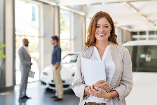 Satisfied saleswoman in car dealership