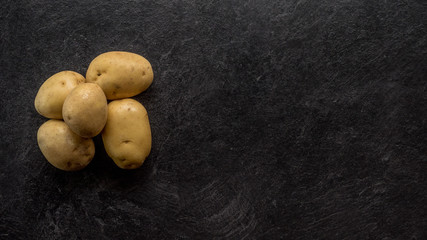 Different cuts of potatoes on a black textured background.