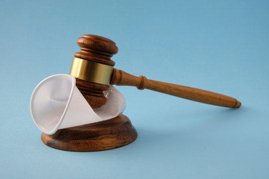 Judges gavel breaks plastic cup. Concept of  law on  prohibition of disposable tableware.