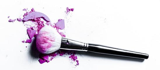 Brush with crushed eyeshadow and powder close-up isolated on white background