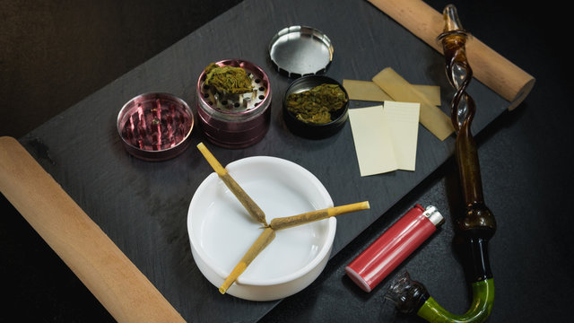 Marijuana joints lie in the ashtray. Smoking pipe, grinder, cannabis.