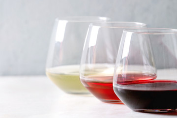 Variety of wine. Red, rose and white wine in old fashion glasses in row on white marble table. Copy space