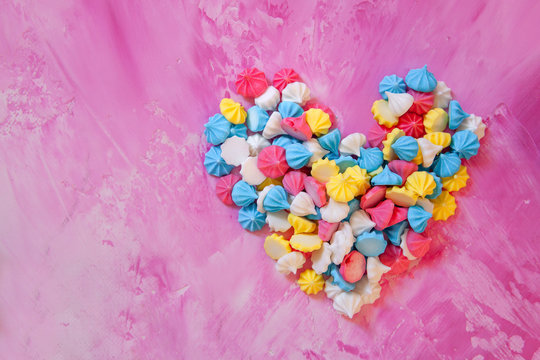 Pastel colored merengues cakes in heart shape on pink background from above