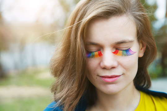 portrait of happy smiling beautiful young woman with rainbow lgbtq eyelashes
