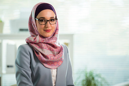 Beautiful young working woman in hijab, suit and eyeglasses standing in office, smiling. Portrait of confident muslim businesswoman. Modern office with big window, man working at desk on background.