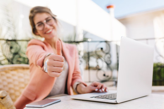 Cute young woman, student, business lady showing thumbs up, well done, sitting in outdoor cafe on terrace with laptop. Wearing pink smart clothes.