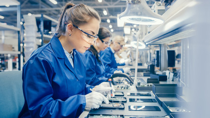 Woman Electronics Factory Worker in Blue Work Coat and Protective Glasses is Assembling Smartphones with Screwdriver. High Tech Factory Facility with more Employees in the Background.