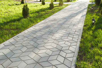The footpath in the park is paved with diamond shaped concrete tiles. On the lawn - small decorative lights. Fototapete