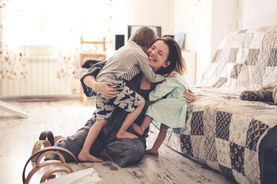 Happy mother hugs her children siblings on floor