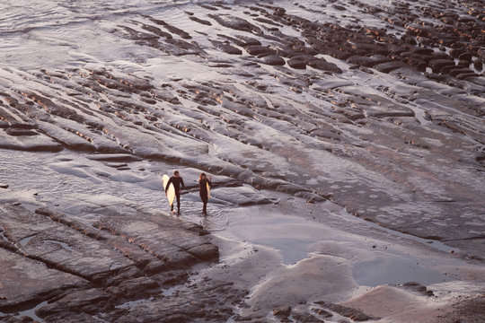Surfers walking on tide pools at sunset