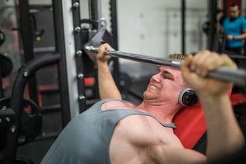 Bodybuilder pushes his limits on the barbell at the gym