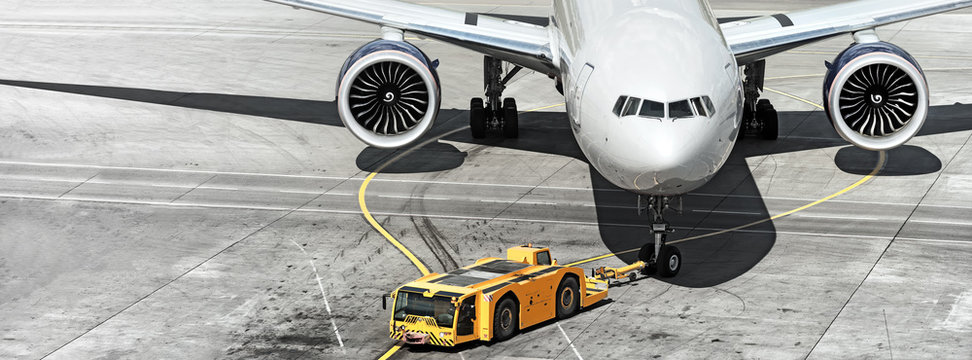 airplane on airport runway with pushback tractor attached to plane nose gear aerial top front view passenger jet engine aircraft towing by ground vehicle to terminal gate black and white wide banner