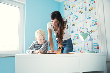 Mother helping son doing homework at desk
