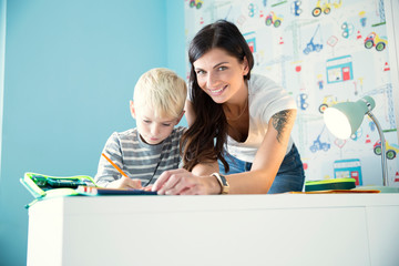 Portrait of smiling mother helping son doing homework at desk