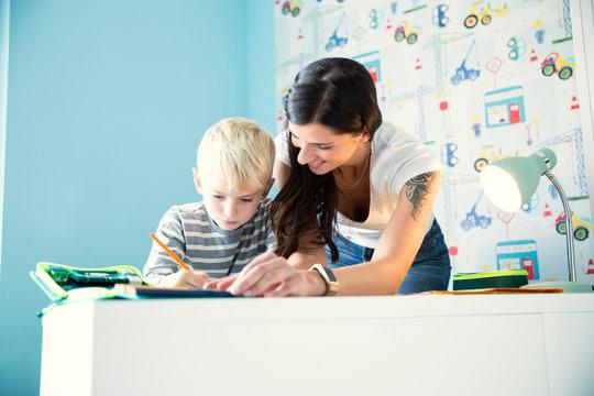 Mother helping son doing homework at desk