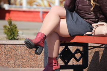 Thick female legs sitting on a bench in the Park on a spring day