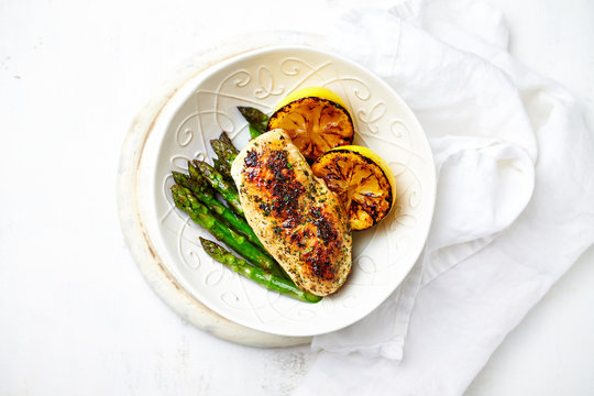 Herb chicken fillet with roasted asparagus and lemon in a bowl. Flat lay