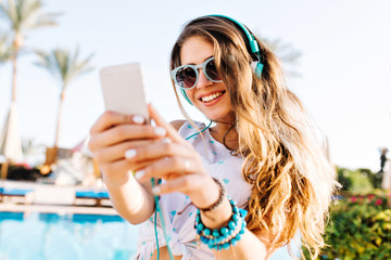 Smiling long-haired girl in sunglasses and earphones making photo of beautiful landscape with exotic palm trees. Joyful tanned young woman with phone chilling out near the pool in sunny morning