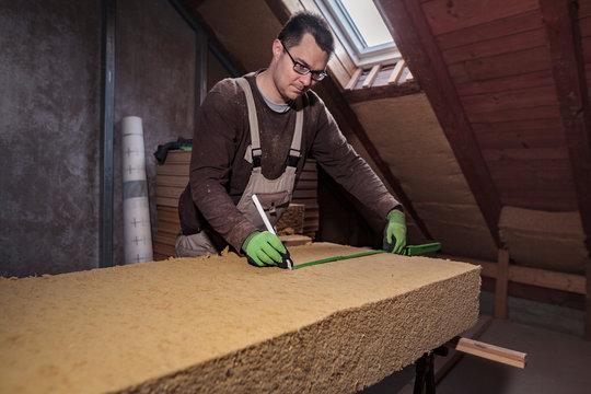Roof insulation, worker measuring wood fiber insulation