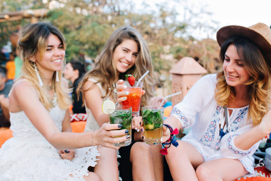 Portrait of three stylish laughing girls in white clothes resting in the park with glasses on foreground. Gorgeous young women having fun after work, sitting in open-air restaurant and drink cocktails