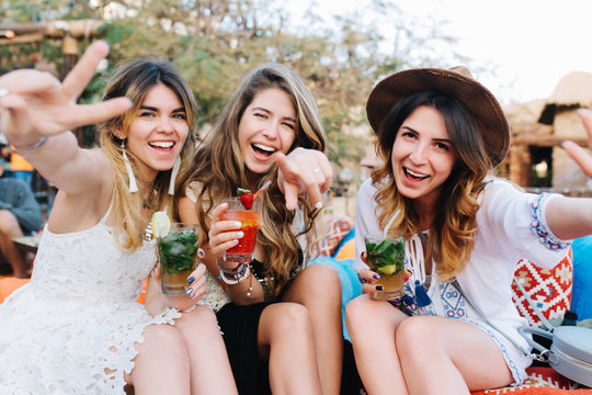 Attractive long-haired girls in stylish attires and accessories drink cocktails and posing with hands waving. Portrait of laughing sisters holding glasses of soda, having fun on picnic in summer day.