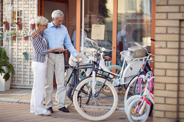 Senior couple shopping new bicycle in bike shop.