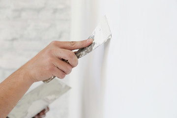 Plastering wall with putty-knife, close up image. Fixing wall surface and preparation for painting.